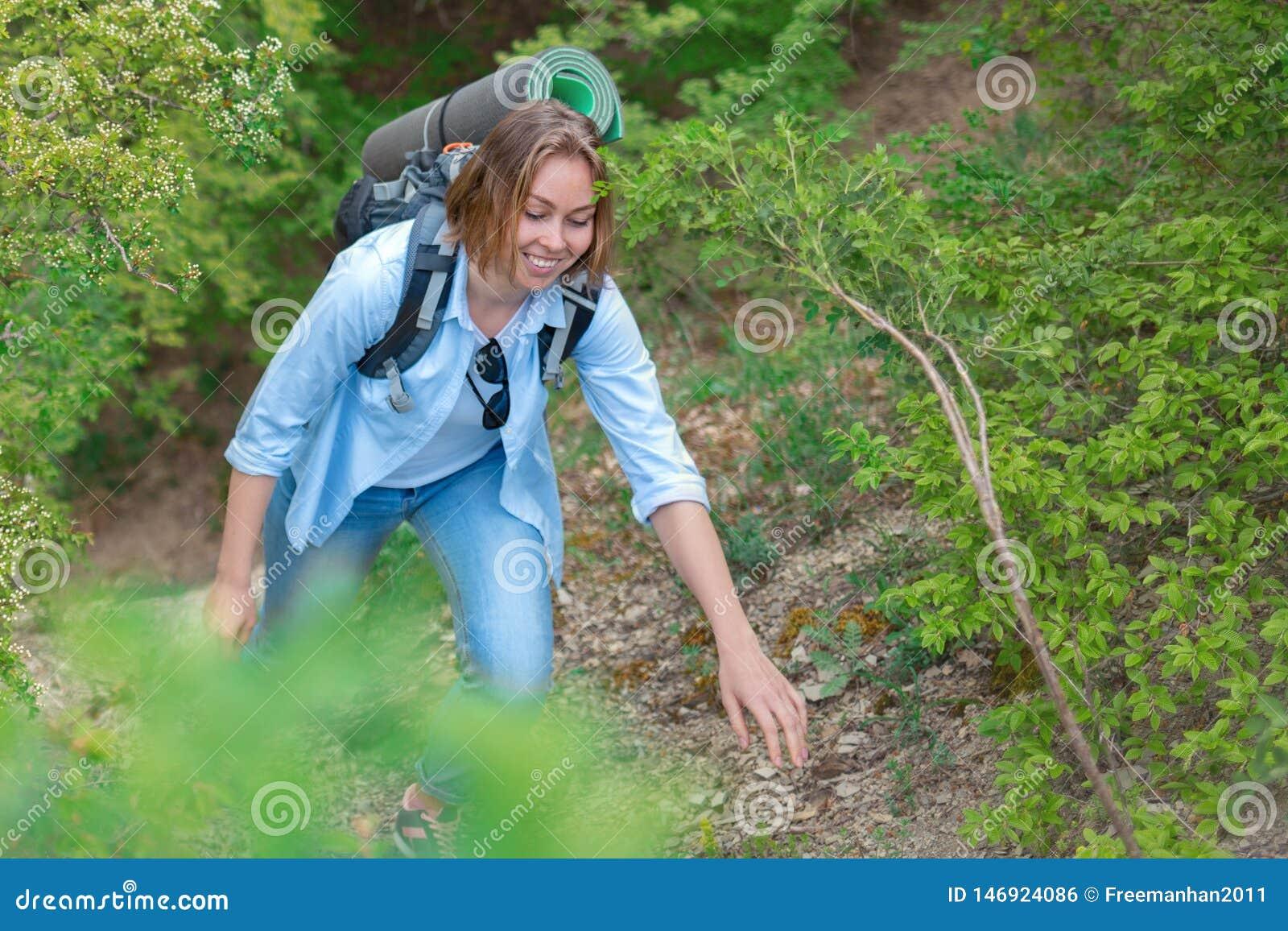 Le kvinnan som klättrar på en bergbana V?xter och tr?d i bakgrunden Aktiv sportar och turism close upp