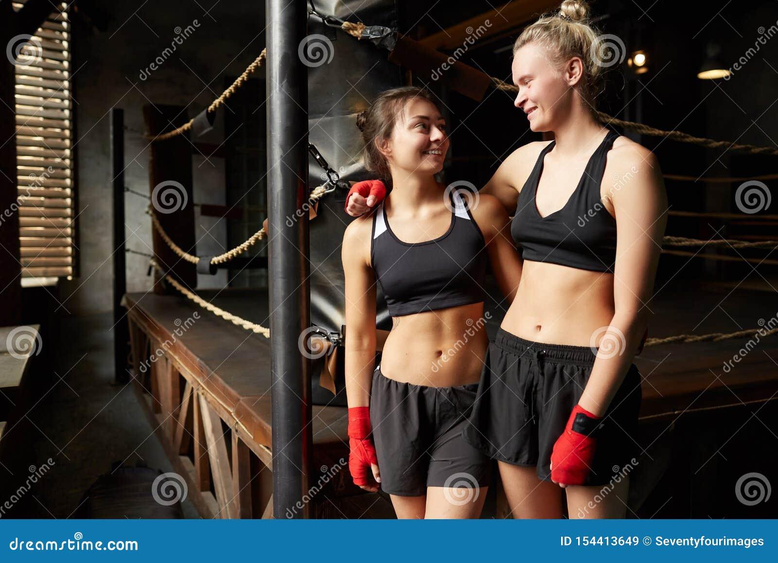 Le kvinnliga boxare som poserar vid cirkeln
