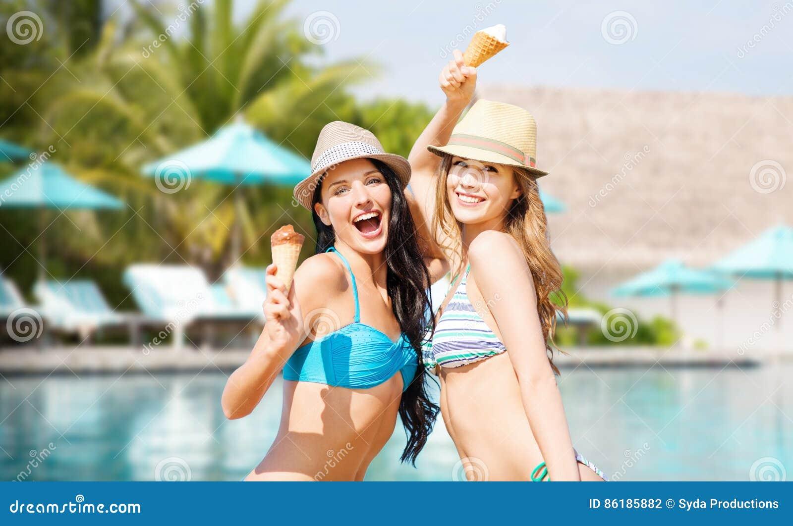 Le kvinnor som äter glass över simbassäng