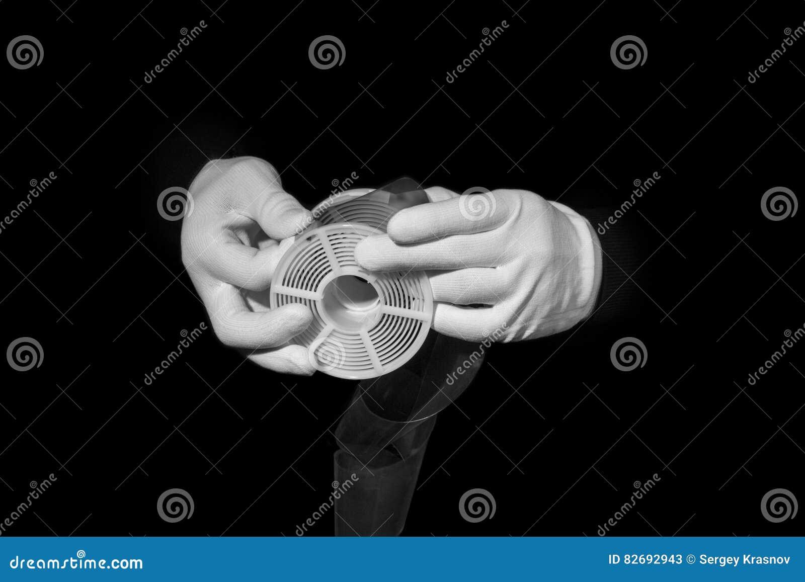 Le laboratoire, mains dans les gants blancs tiennent un noir et un film, chambre noire, developmen