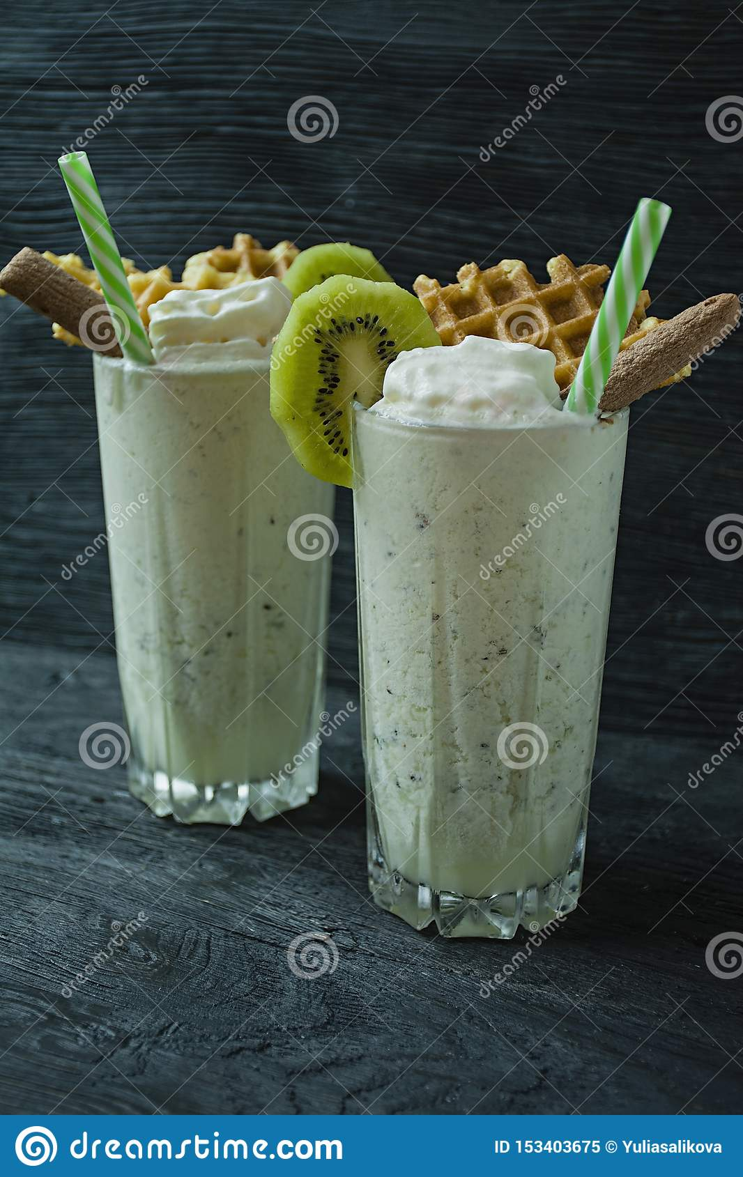Le lait de poule avec le kiwi, la crème glacée et la crème fouettée, guimauves, biscuits, gaufres, a servi dans une tasse en verr