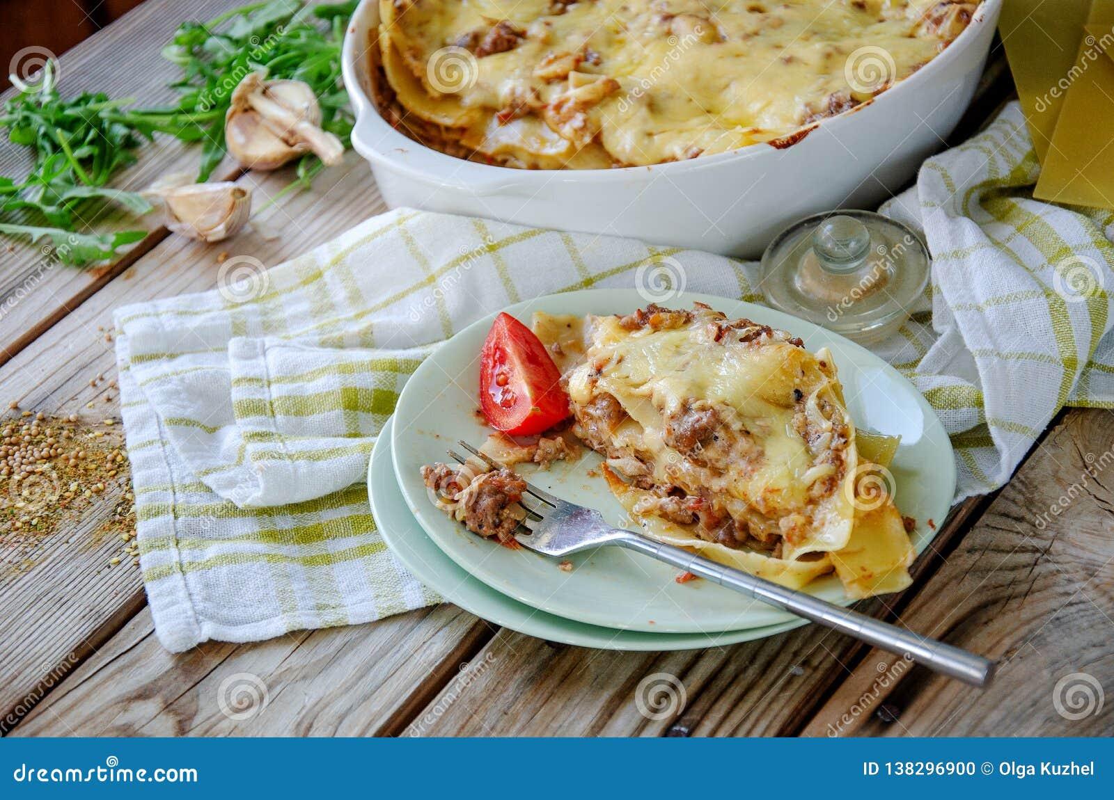 Le lasagne al forno tradizionali hanno fatto con la salsa bolognese e la salsa besciamella del manzo tritato con pepe e le erbe