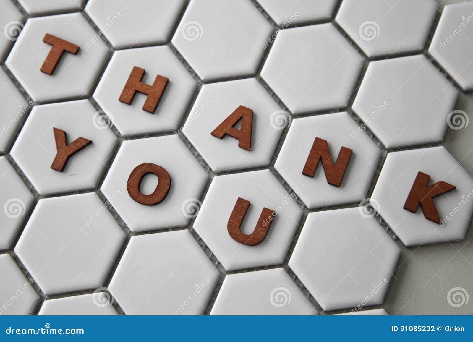 Le lettere che formano le parole vi ringraziano sulle mattonelle a
