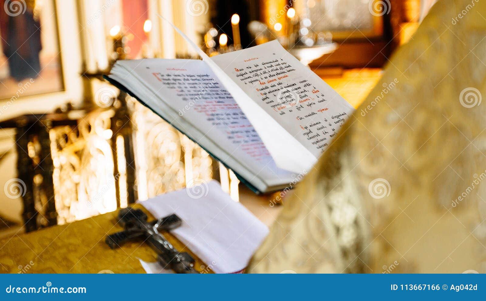 Le livre chrétien d église de lecture de prêtre, prêtre lit une prière au-dessus de t