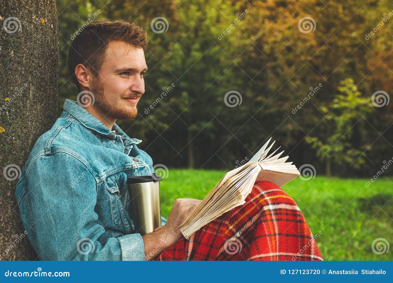 Le livre de lecture de sourire de jeune homme extérieur avec un plaid rouge chaud et une tasse de thé l automne de fond vacations