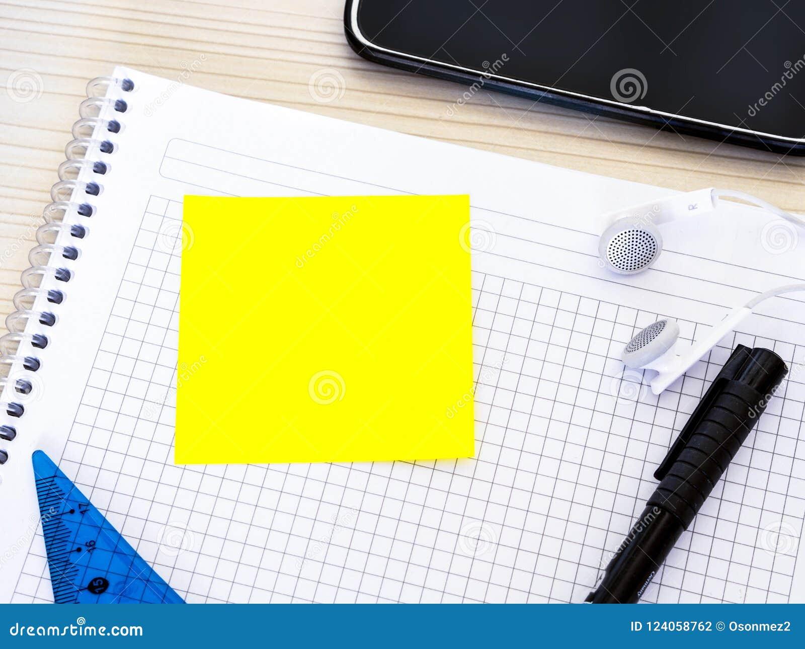 Le livre de mathématiques sur la table de cours et l étudiant chassent des matériaux avec le papier de note