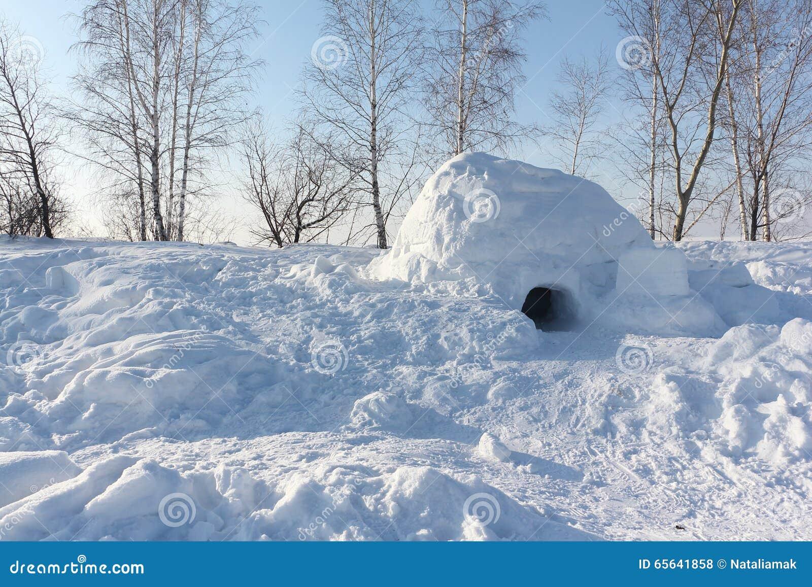 Le logement un igloo sur une clairière de neige pendant l hiver au coucher du soleil