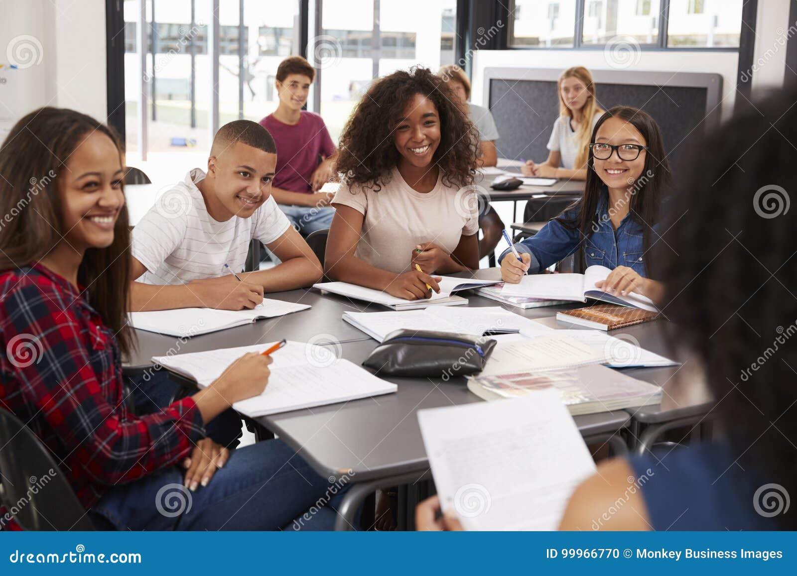 Le lycée badine regarder au professeur s asseyant leur bureau