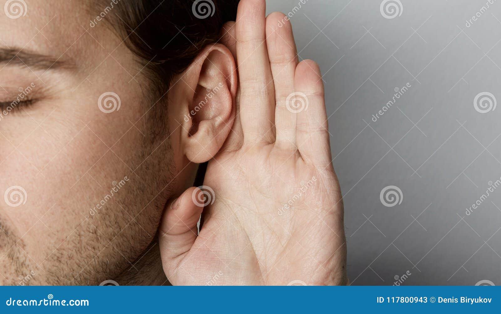 Le mâle de écoute tient sa main près de son oreille au-dessus de fond gris