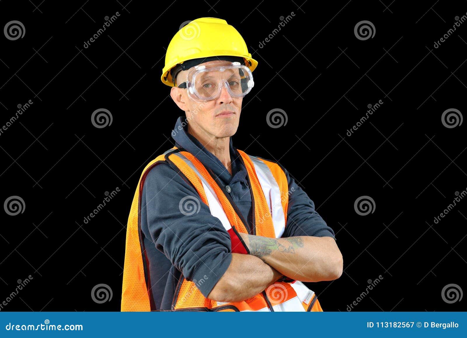 Le mâle de travailleur de la construction dans le chapeau de sécurité jaune, gilet orange, gants rouges, google et étant prêt pou
