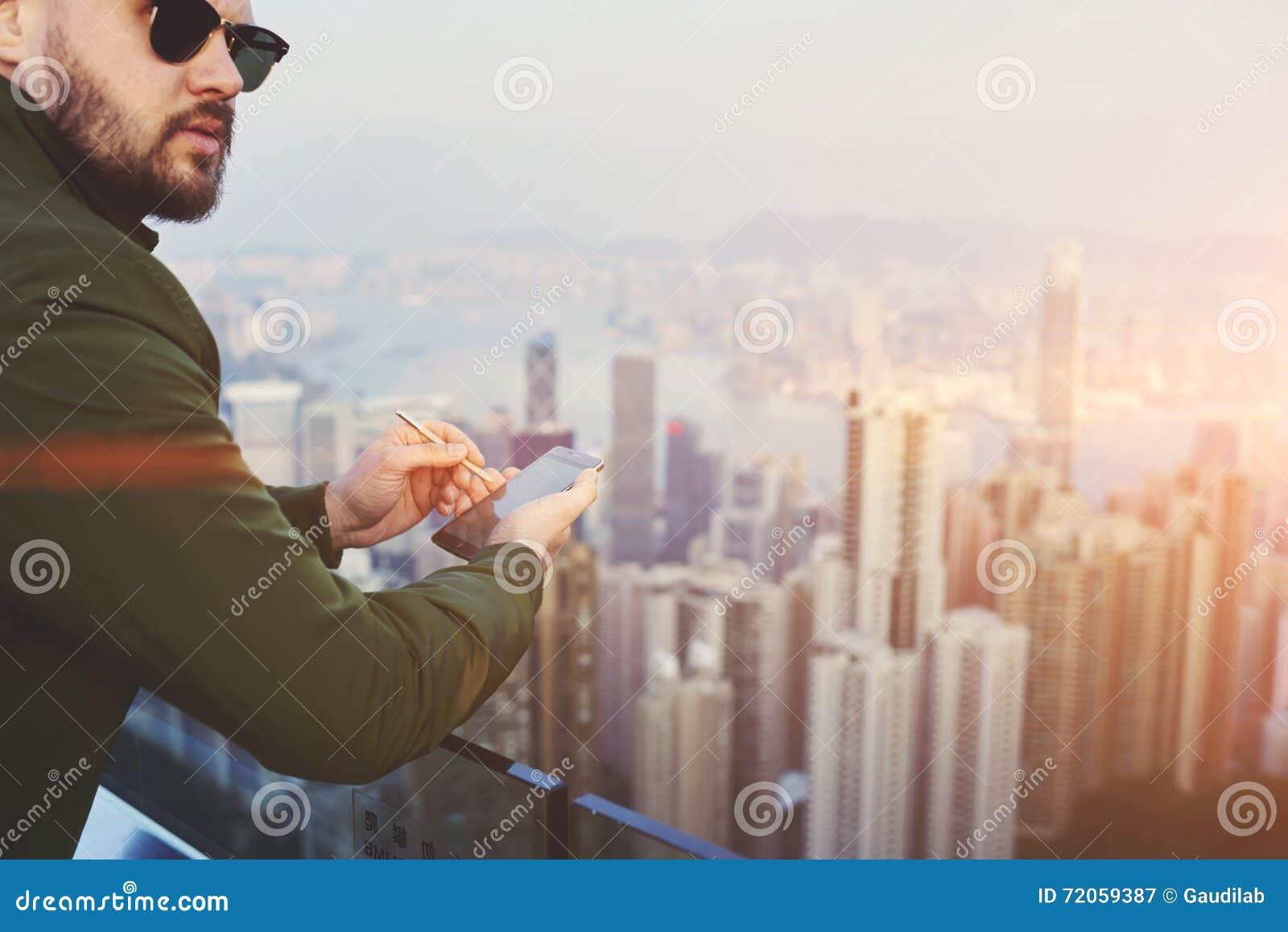 Le mâle sûr utilise le téléphone de cellules