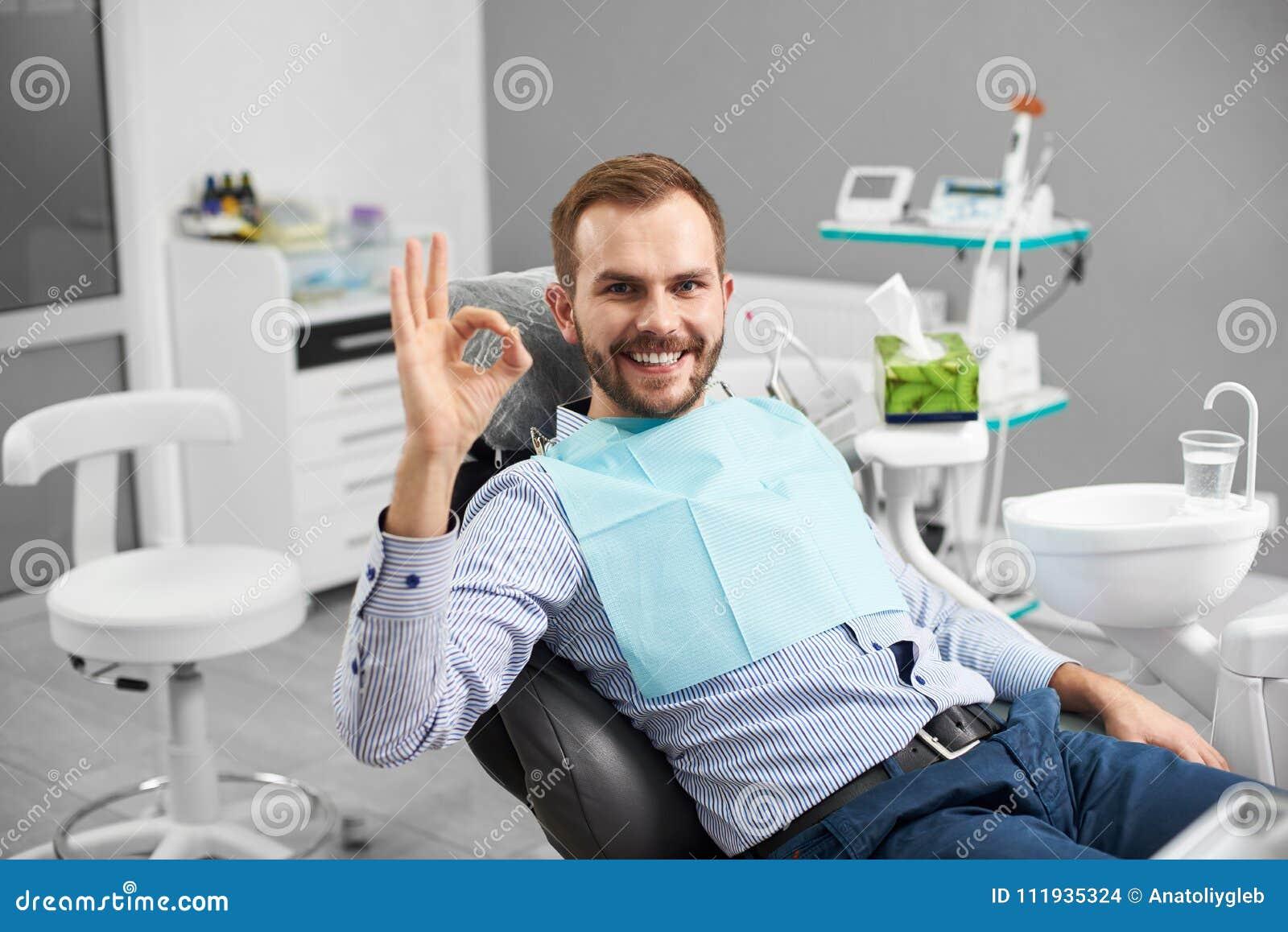 Le mâle sourit à l appareil-photo et montre le signe correct étant satisfaisant après traitement de dents en art dentaire moderne