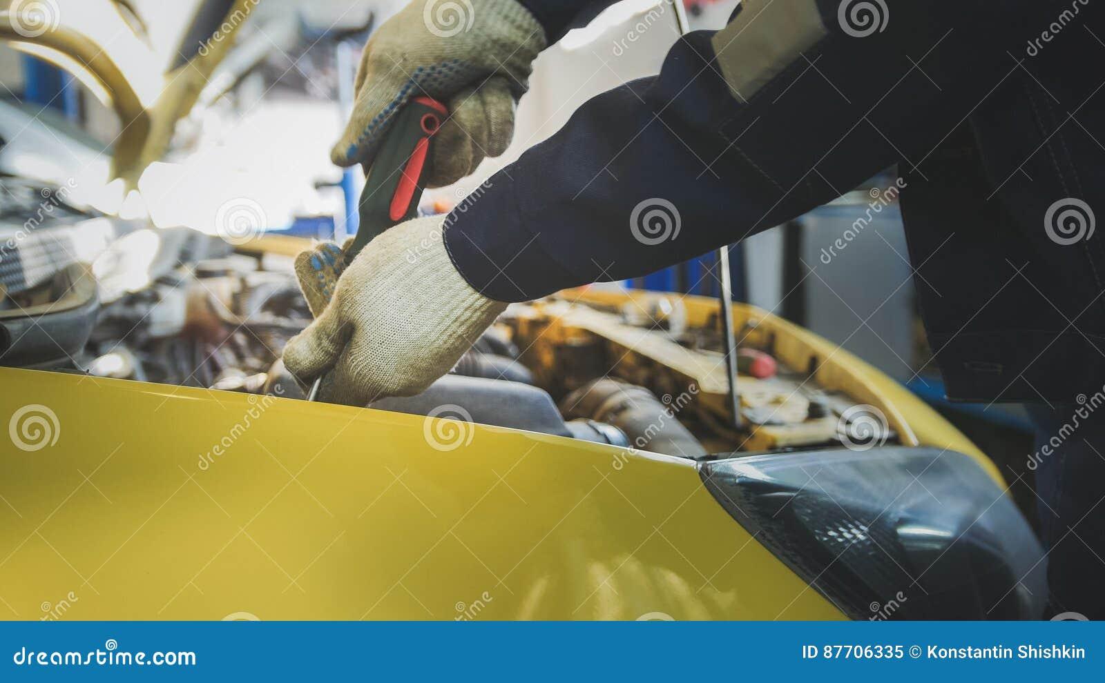 Le mécanicien dévisse le détail de la voiture dans le capot - service d automobile réparant, fin