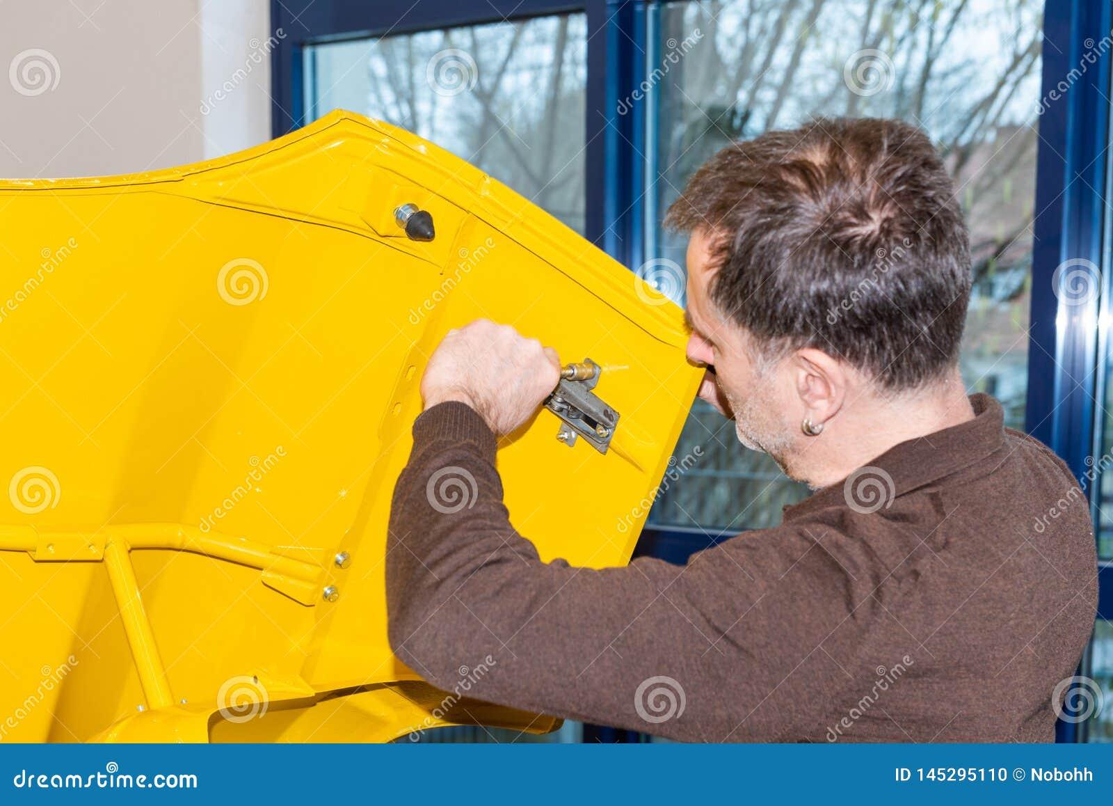 Le mécanicien de voiture visse des pièces de voiture ensemble encore après restauration - atelier de réparation de Serie