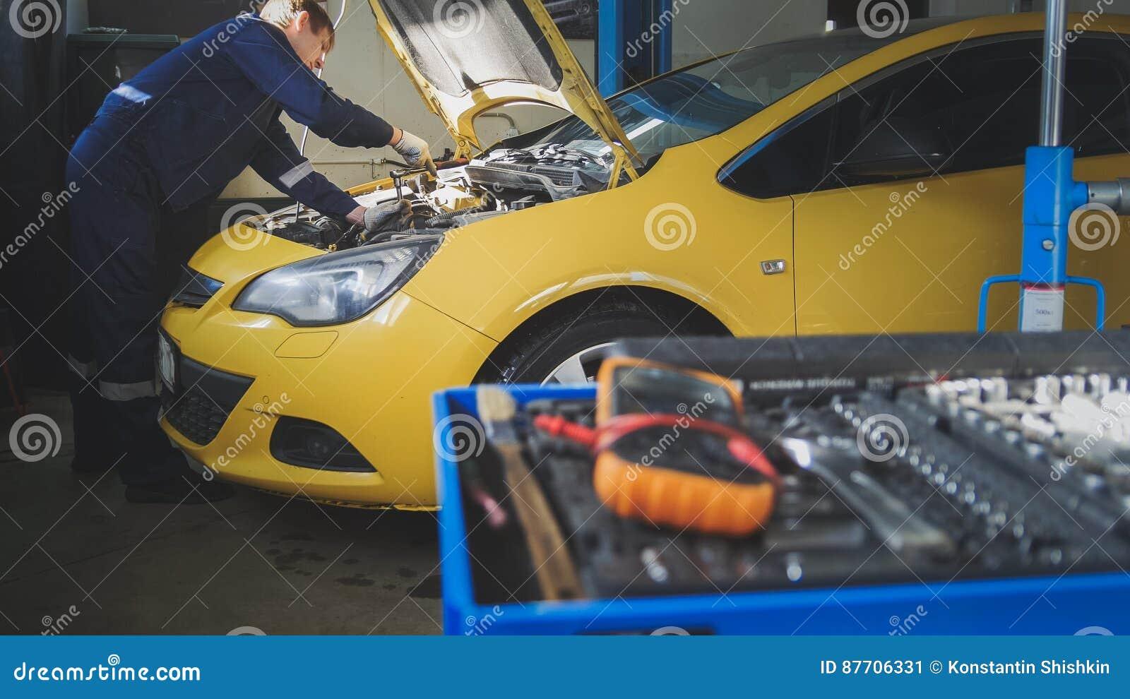 Le mécanicien répare un automobile dévisse le détail de l automobile - service de garage
