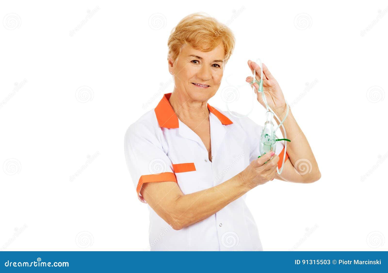 Le médecin ou l infirmière féminin plus âgé de sourire tient le masque à oxygène