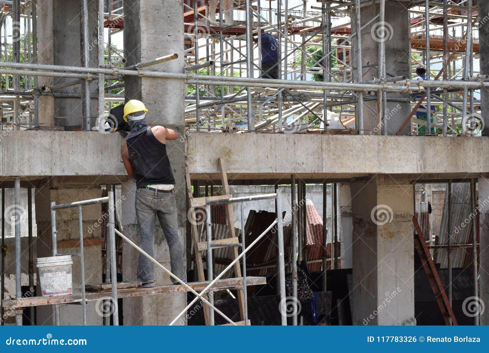 Le maçon de construction de bâtiments faisant plâtrant le travail se tenant sur l échafaudage siffle au chantier