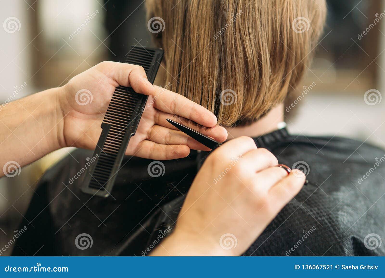 Le maître coupe des cheveux et la barbe des hommes dans le raseur-coiffeur, coiffeur fait la coiffure pour un jeune homme