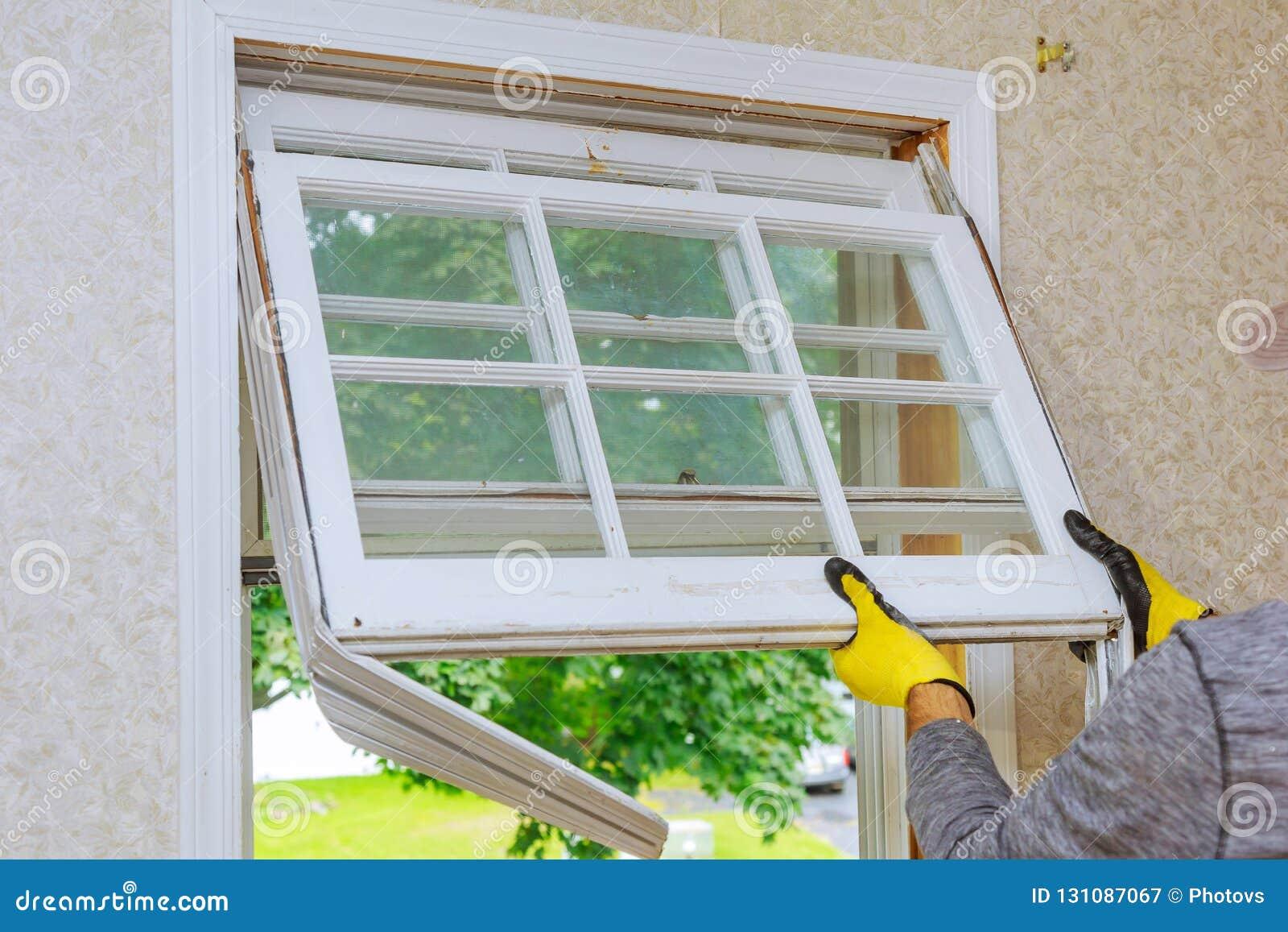 Le maître enlève de vieilles réparations à la maison, fenêtres de rechange