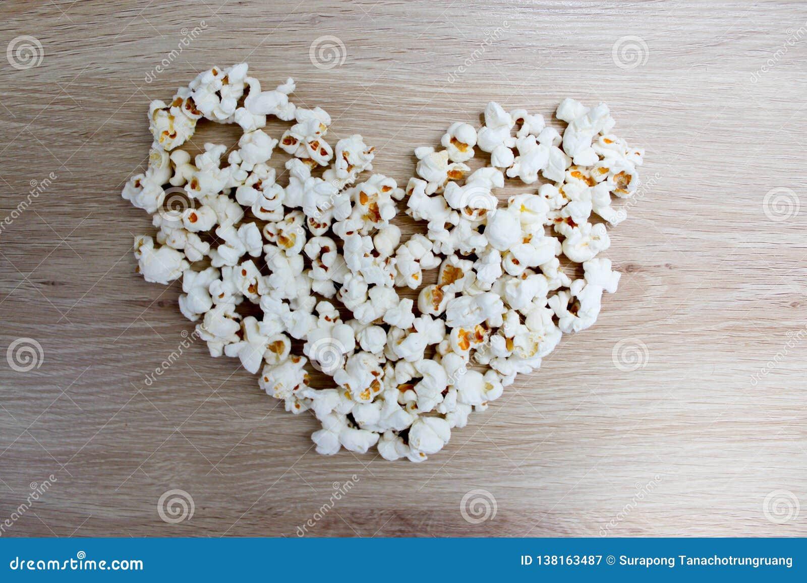 Le maïs éclaté a arrangé dans une forme de coeur sur en bois