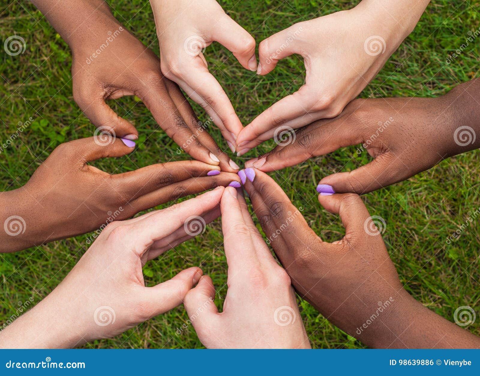 Le mani in bianco e nero nel cuore modellano, concetto interrazziale di amicizia