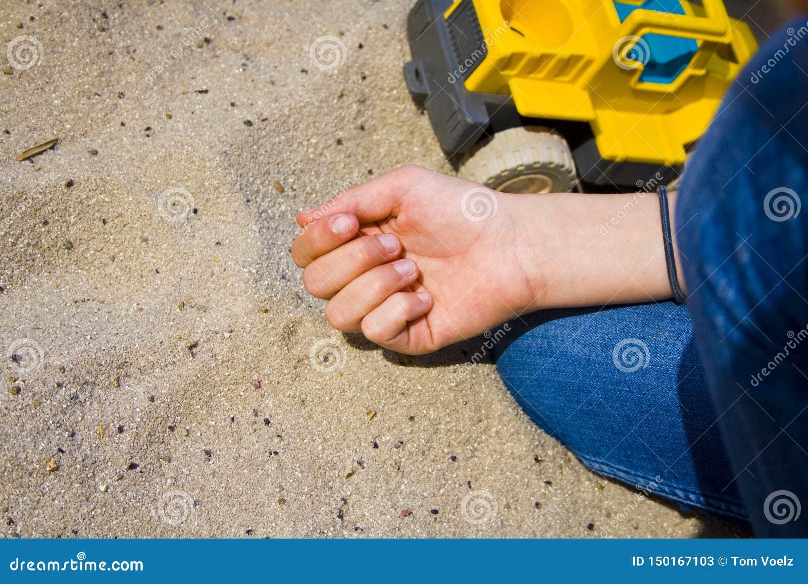 Le mani dei bambini nella sabbia mentre giocando