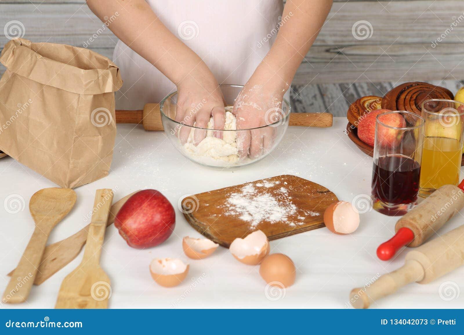 Le mani dei bambini producono la torta da pasticceria