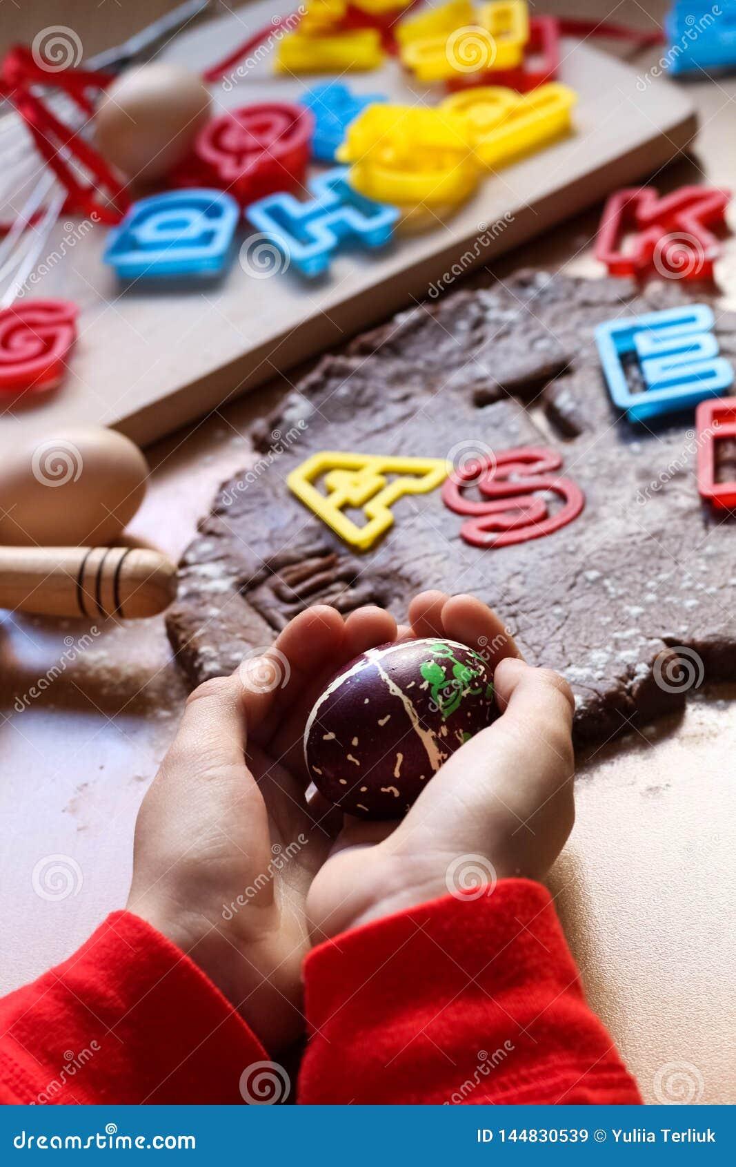 Le mani dei bambini tengono un uovo di Pasqua decorato Cottura dei biscotti tradizionali di Pasqua Uova di Pasqua Concetto dell a