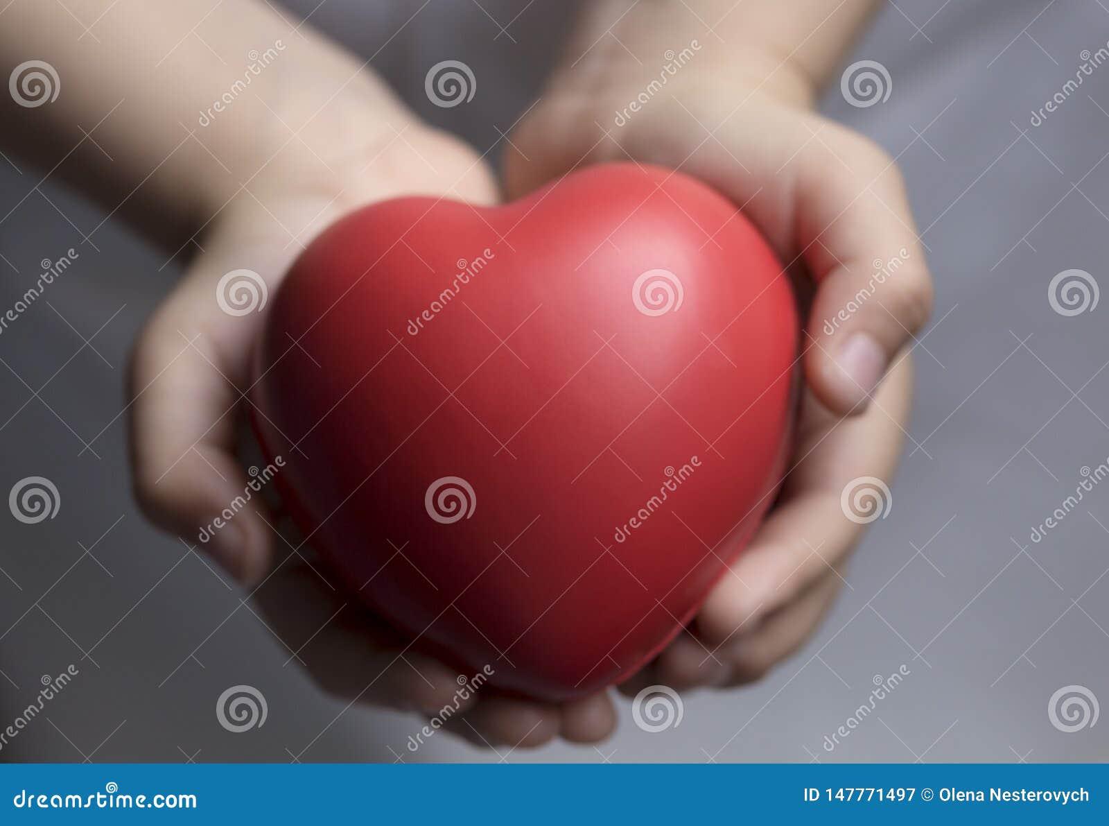 Le mani del bambino che tengono il cuore rosso, sanità, concetto di assicurazione della famiglia e donano, il giorno del cuore de