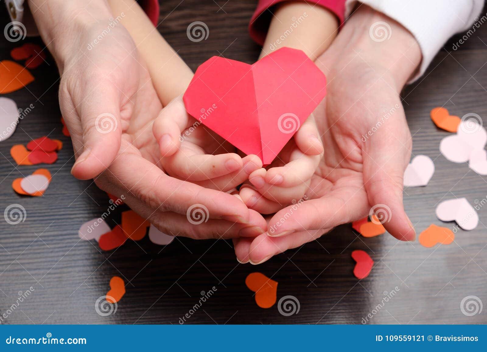 Le mani del bambino e dell adulto che tengono il cuore modellano, sanità, concetto di assicurazione della famiglia e donano