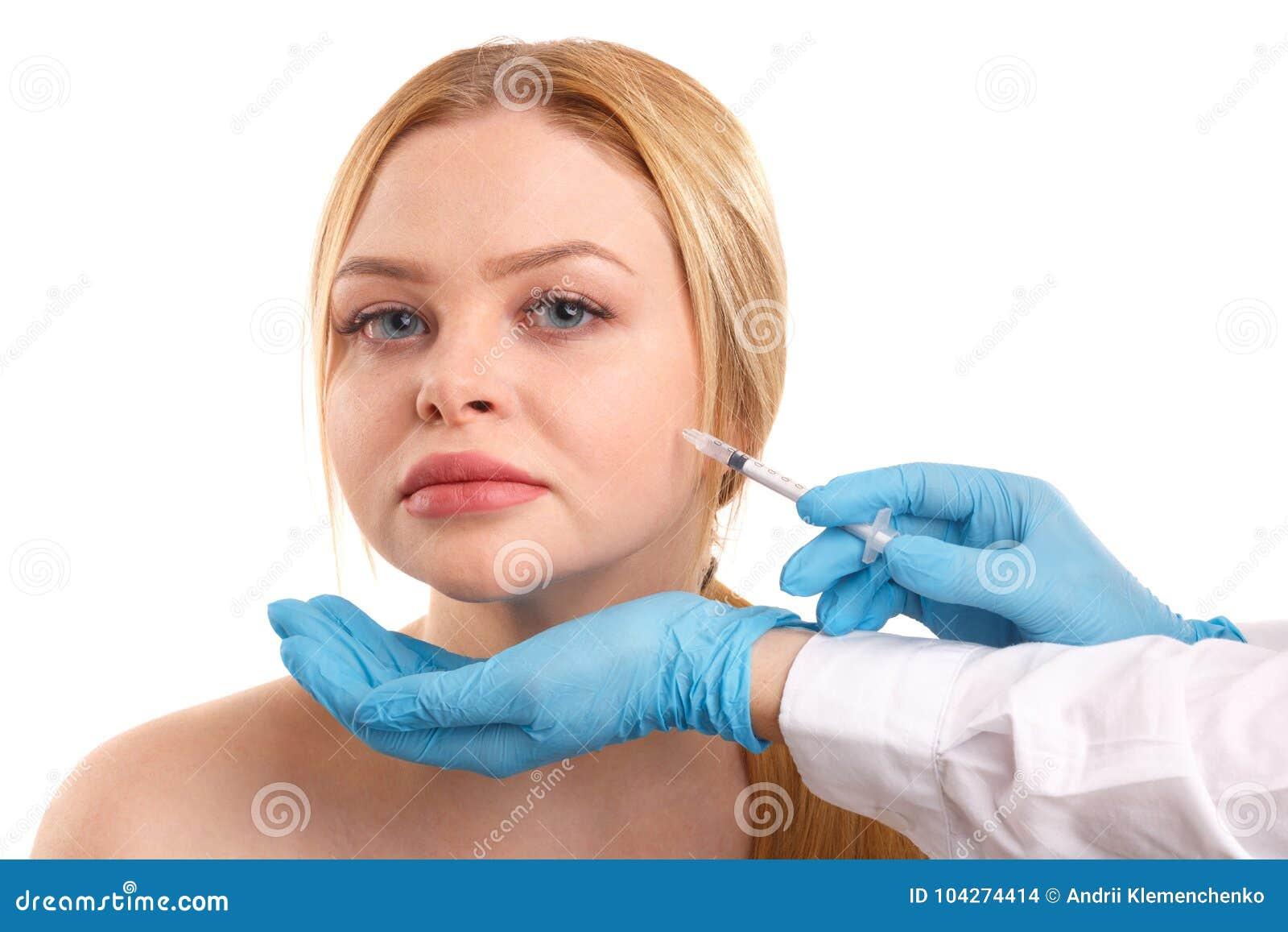 Le mani del ` s di medico fanno le iniezioni di Botox di bella donna nell area della guancia Isolato