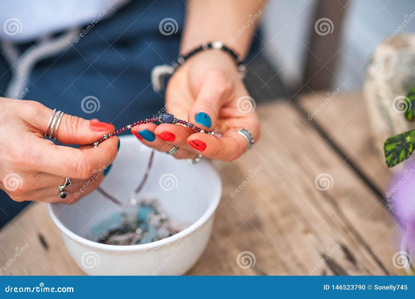 Le mani del tocco della ragazza i gioielli fatti a mano Ragazza e gioielli La donna fatta a mano che decora le pietre si chiude s