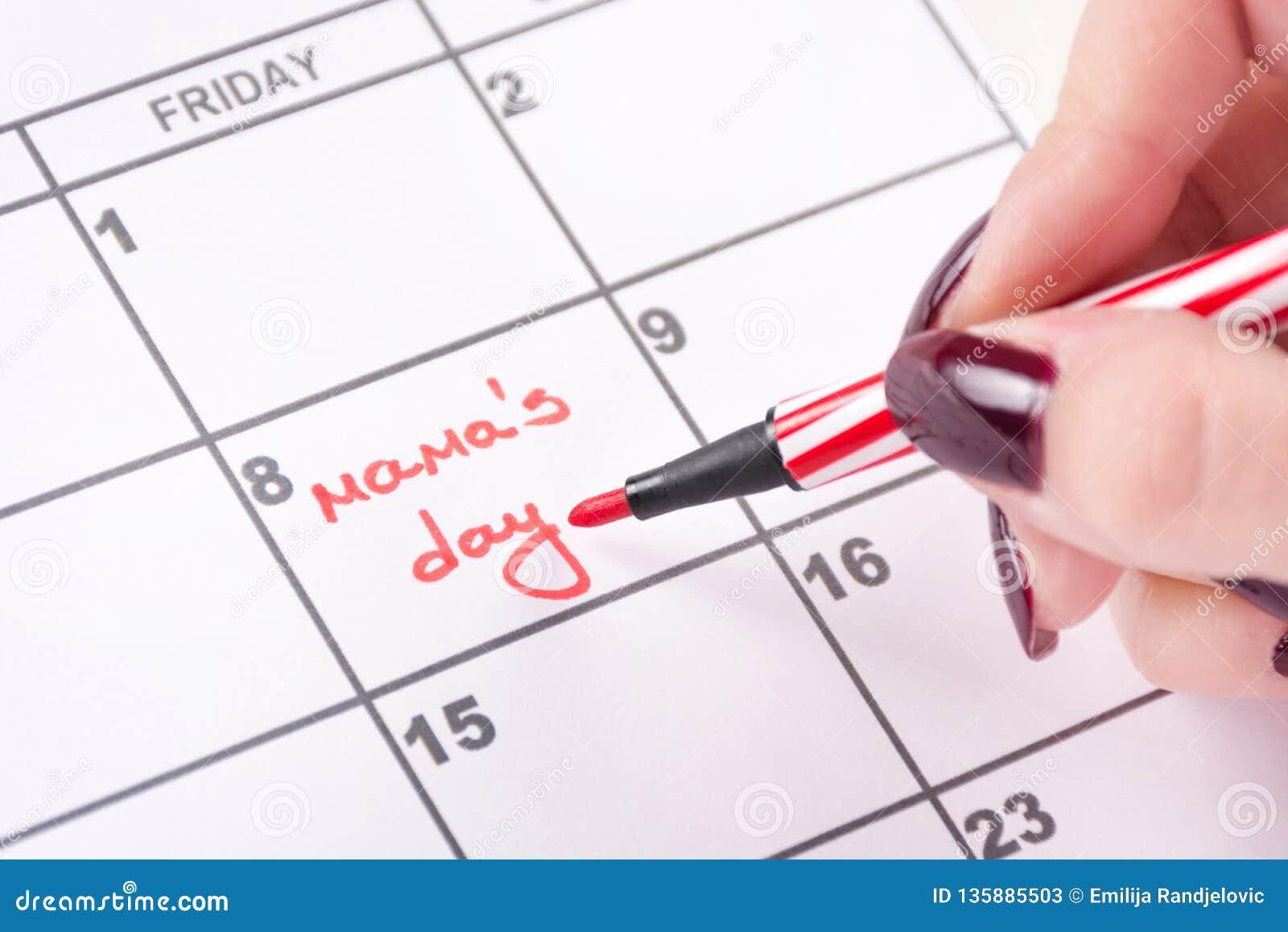Le mani della donna con la penna ritenuta rossa scrive il giorno di mamme di parole in calendario