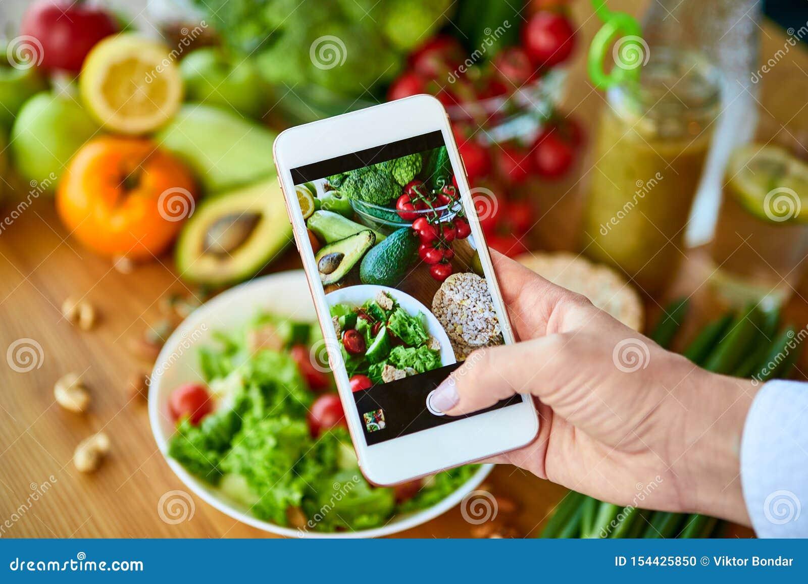 Le mani della donna prendono la foto dell alimento dello smartphone dell insalata delle verdure con i pomodori ed i frutti Fotogr