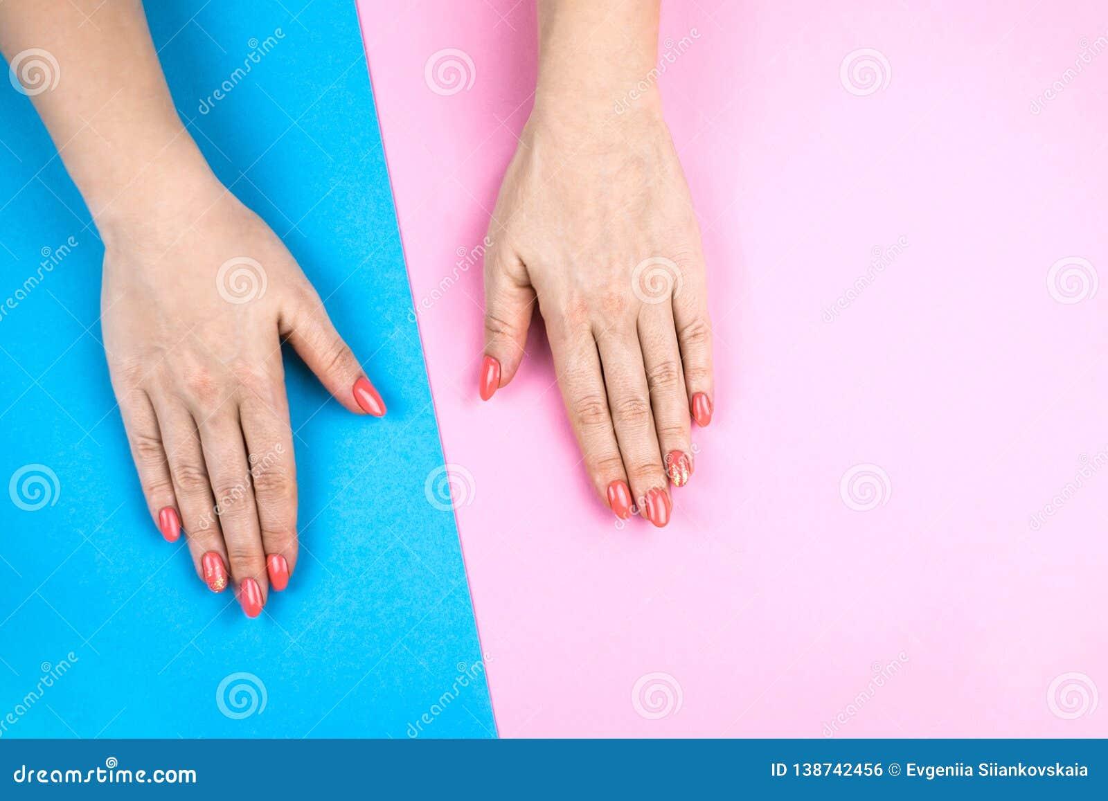 Le mani della giovane donna adorabile su fondo colorato