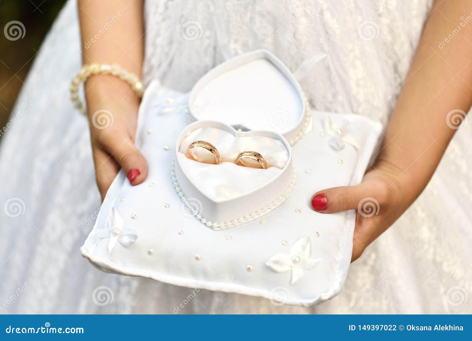 Le mani della ragazza tengono le fedi nuziali in una scatola in forma di cuore