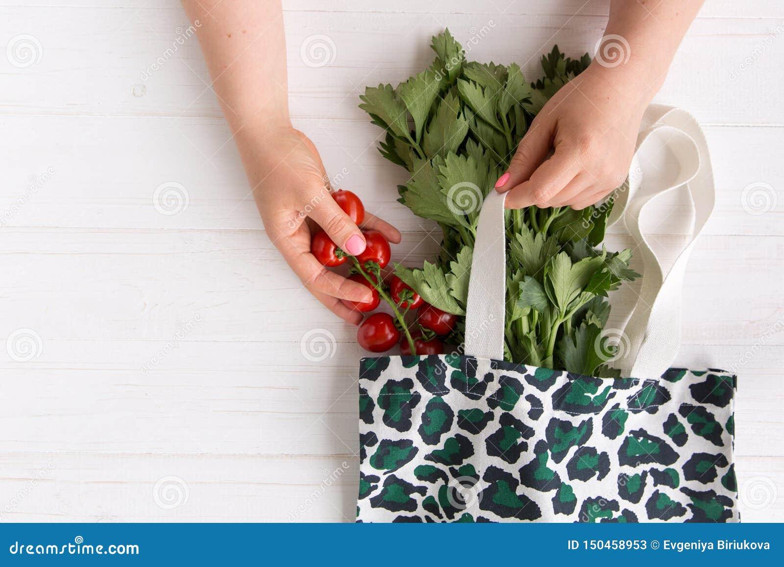 Le mani di una donna eliminano i pomodori organici freschi dal sacchetto della spesa di Eco con la stampa d avanguardia del model