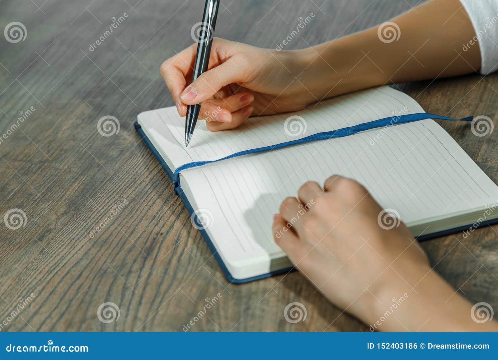 Le mani femminili stanno scrivendo in un taccuino