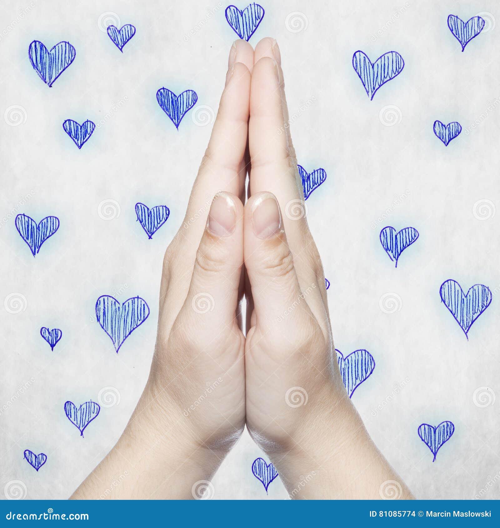 Le mani hanno piegato nella preghiera, poi con i cuori blu