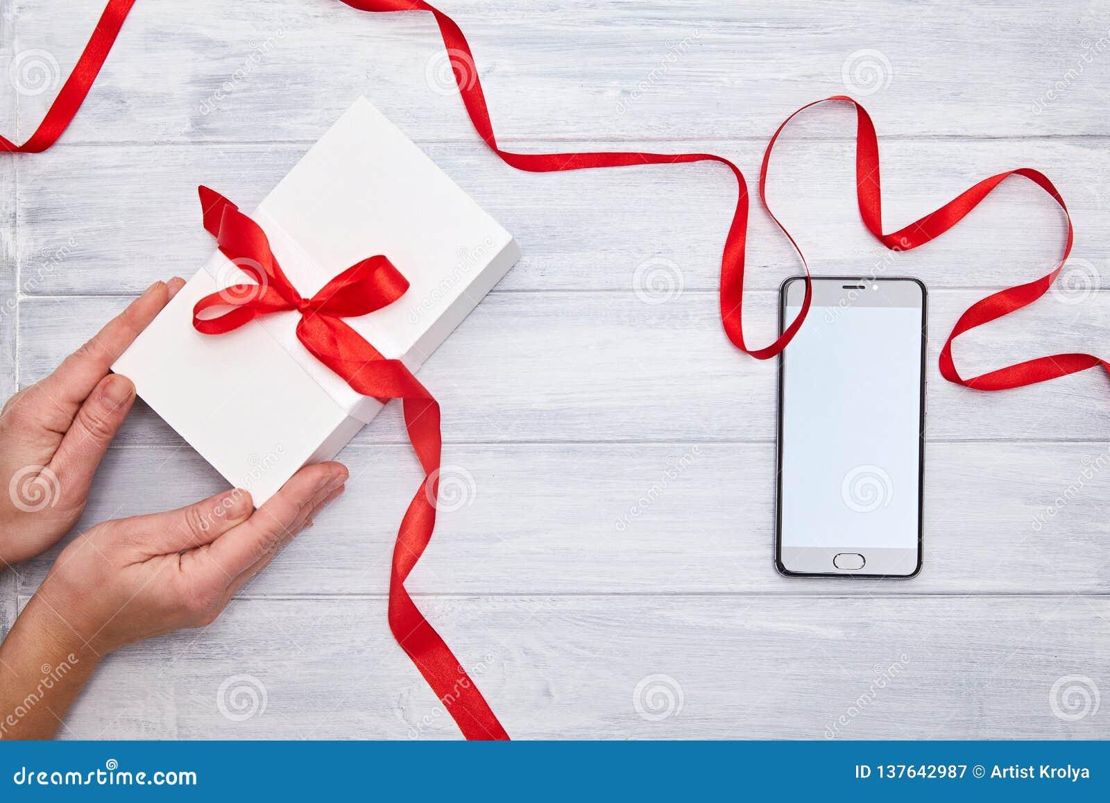 Le mani tengono il contenitore di regalo con il nastro rosso e lo smartphone su un fondo del woodem