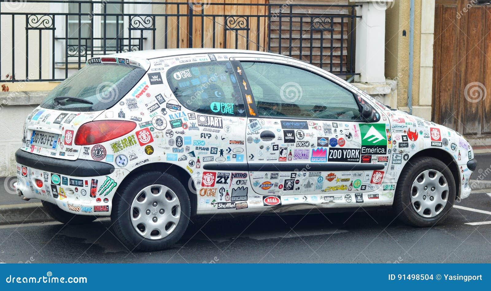 LE MANS, FRANCIA - 25 de abril de 2017: las etiquetas engomadas del coche cubren un coche blanco Peugeot