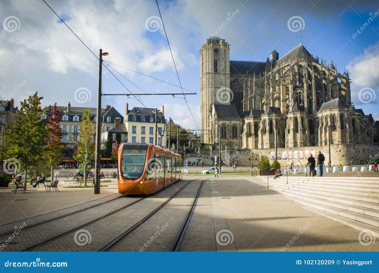 LE MANS, FRANKRIJK - OKTOBER 08, 2017: Roman kathedraal van Saint Julien met een oranje tram in Le Mans, Frankrijk