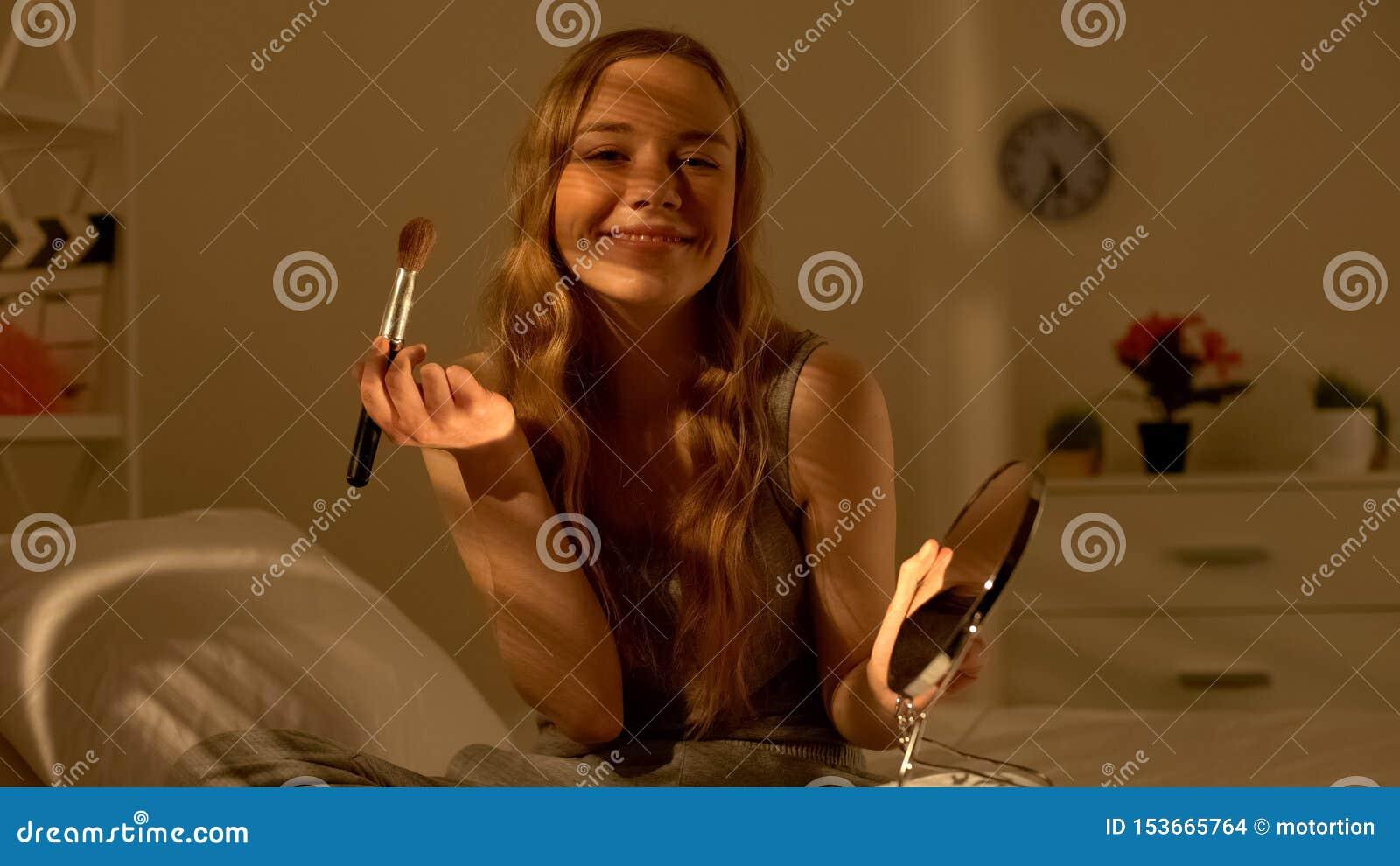 Le maquillage de application femelle de l adolescence joyeux rougissent et souriant à la caméra, beauté naturelle