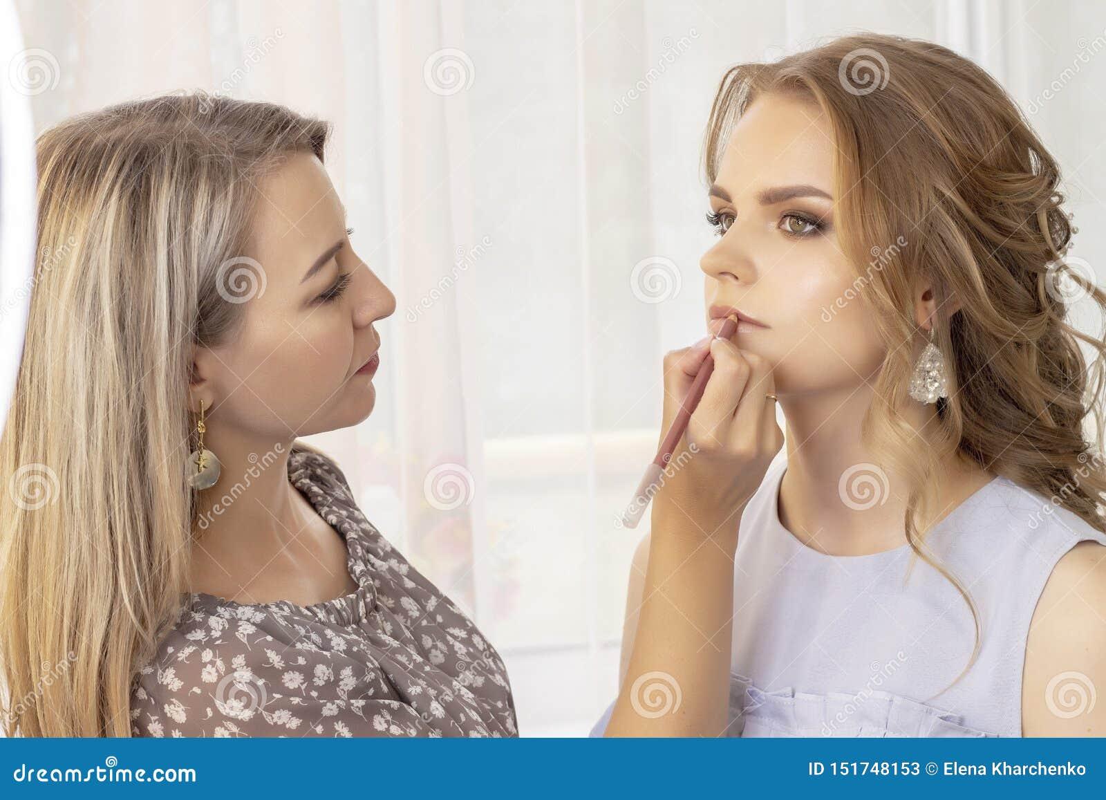 Le maquilleur met composent sur le modèle de fille épousant le maquillage, égalisant le maquillage, maquillage naturel l artiste