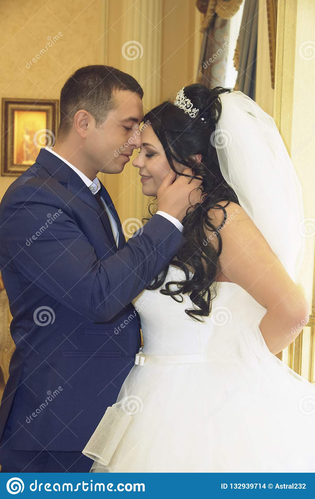 Le marié étreint doucement la jeune mariée