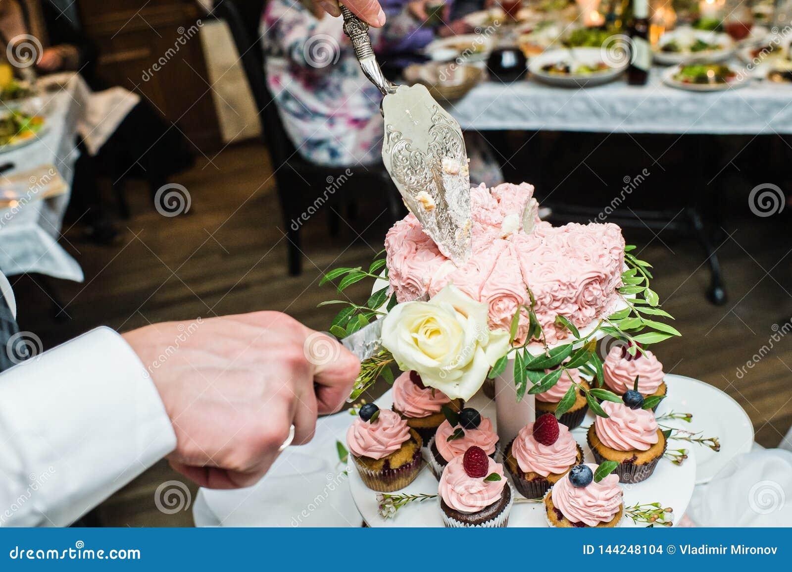 Le marié coupe le gâteau l épousant rose