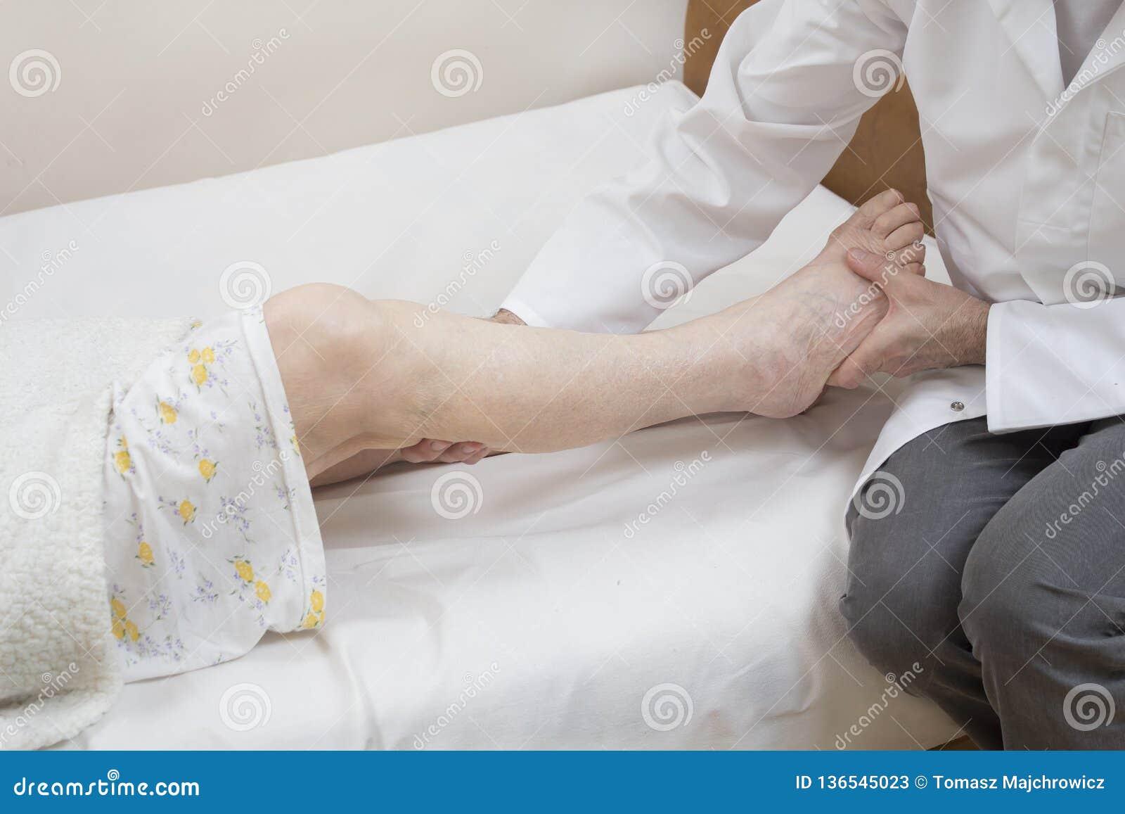 Le masseur masse le veau de dame âgée se trouvant sur un lit sur une feuille blanche