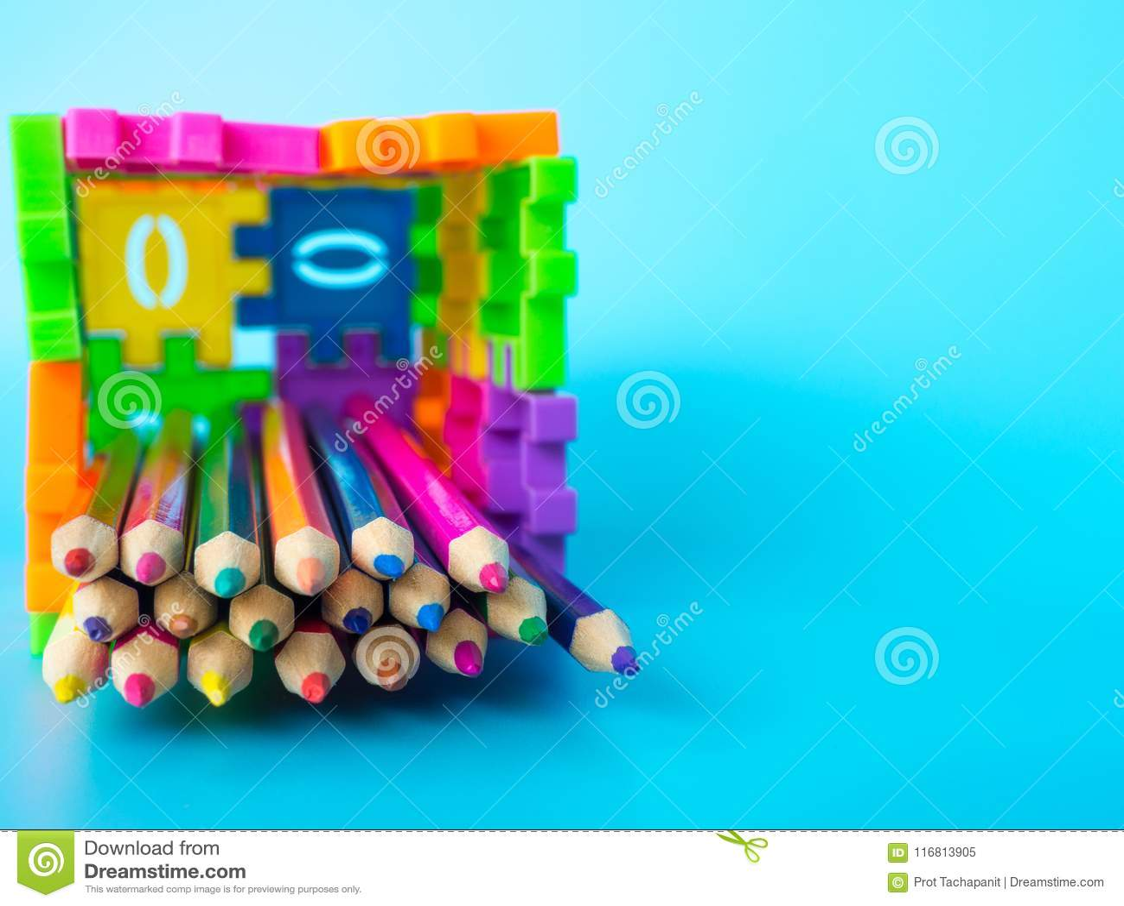 Le matite di colore in variopinto del supporto della matita fanno il numero di puzzle della forma su fondo blu Concetto di formaz