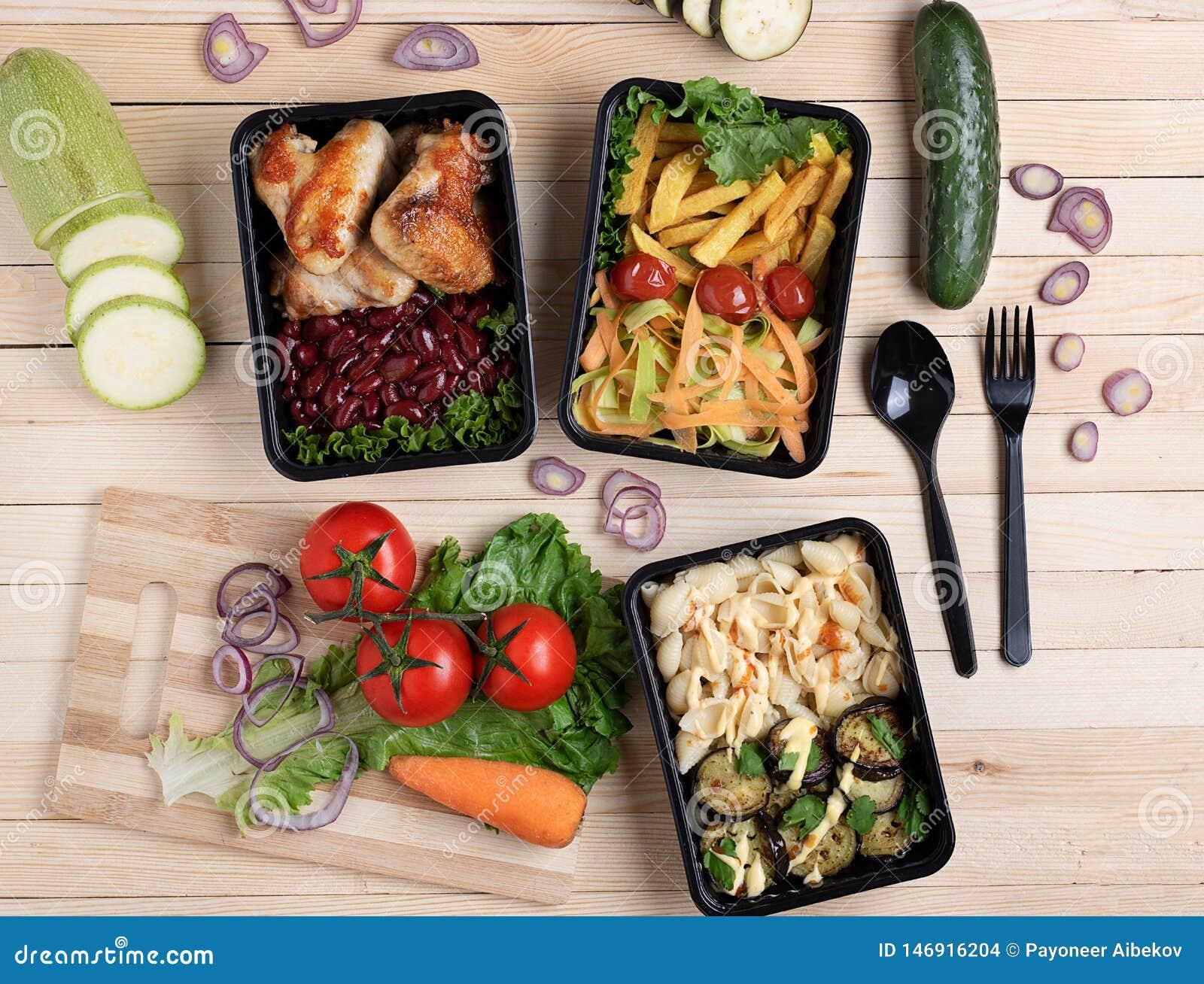 Le melanzane fritte in contenitore con le ali di pollo arrostite sopra kitcen il bordo, i pomodori, lo zucchini ed i micro greens