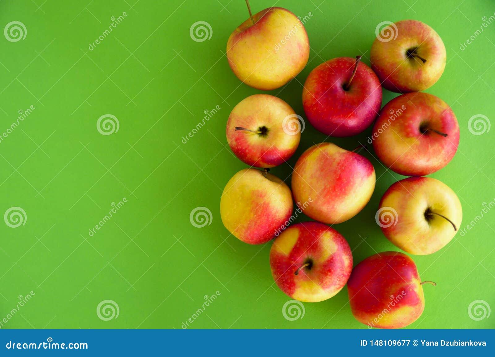 Le mele fresche succose Giallo-rosse si trovano su un fondo verde frutta fresca dal giardino Dieta